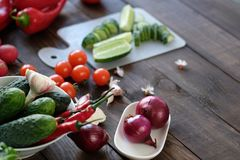 Fresh vegetables sliced for a salad on a cutting board. On an old wooden table Stock Photos
