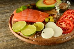 Fresh vegetables and smoked fish on wooden board in rustic kitch. En. Salmon, lime, onions, olives, tomatoes and olive oil. Focus on foreground Royalty Free Stock Photo