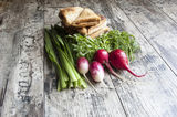 Fresh vegetables and some sandwiches on the old wooden table. Fresh vegetables (onion, radish, dill) and sandwiches, horizontal snapshot stock images