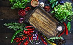 Fresh vegetables, spices and herbs in wooden box in rustic style. Raw organic healthy food concept. Red pepper, onions, garlic, basil and rosemary on white Royalty Free Stock Photos