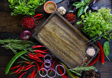 Fresh vegetables, spices and herbs on wooden table and empty cutting board. In rustic style. Raw organic healthy food concept. Red pepper, onions, garlic, basil Royalty Free Stock Photo