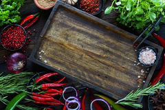 Fresh vegetables, spices and herbs on wooden table and empty cutting board. In rustic style. Raw organic healthy food concept. Red pepper, onions, garlic, basil Stock Images