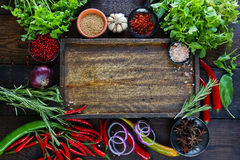 Fresh vegetables, spices and herbs on wooden table and empty cutting board. In rustic style. Raw organic healthy food concept. Red pepper, onions, garlic, basil Royalty Free Stock Photography