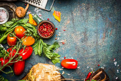 Fresh vegetables and spices ingredients for tasty vegetarian cooking on dark rustic background. Top view Royalty Free Stock Images