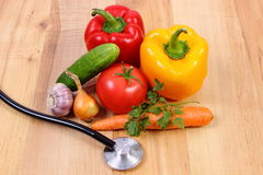 Fresh vegetables and stethoscope on wooden surface, healthy lifestyle and nutrition Stock Images