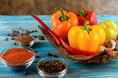 Fresh vegetables,.Sweet red, yellow, green, orange pepper in basket on wooden background.  Red pepper spice  and  black pepper. Sweet red, yellow, green, orange Stock Photo