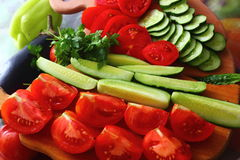 Fresh vegetables on the table. Fon the table on the board are sliced ??fresh cucumbers and tomatoes Stock Image