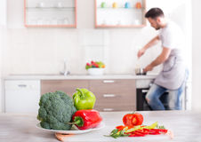 Fresh vegetables on table with man cooking in background Royalty Free Stock Images