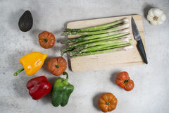 Fresh vegetables on table, tomatoes, garlic, asparagus, avocado. Red pepper, yellow pepper, green pepper. Platter and knife ready to prepare the salad. Raw Stock Photo