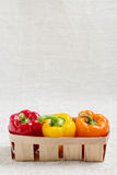 Fresh vegetables. Three sweet peppers in a basket of red, yellow Royalty Free Stock Image