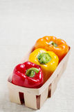 Fresh vegetables. Three sweet peppers in a basket of red, yellow Stock Photography