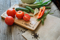 Fresh vegetables tomatoes, cucumber, chili peppers, dill on wooden background. Royalty Free Stock Images