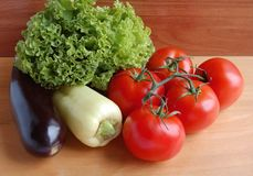 Fresh vegetables tomatoes, eggplants. peppers, lettuce. On a wooden table top Royalty Free Stock Photo