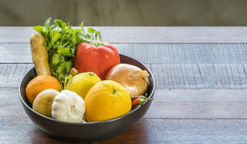 Fresh vegetables in a tray, Courgettes, onion, orange, lemon, to. A tray of Fresh vegetables on a wooden table, Courgettes, onion, orange, lemon, tomato, potato Stock Images