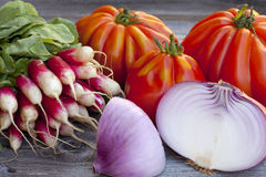 Fresh vegetables from the Weekly Market. Coeur de Boeuf Tomatoes, large red Onions and Radishes fresh from the Weekly Market on a old wooden Table Royalty Free Stock Photos