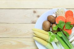 Fresh vegetables in a white dish are placed on a brown wood floo. R and have copy space for your design foods concept in work Royalty Free Stock Images