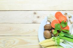 Fresh vegetables in a white dish are placed on a brown wood floo. R and have copy space for your design foods concept in work Royalty Free Stock Photo