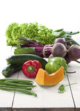 Fresh vegetables on white rustic table. Fresh vegetables (pumpkin, green beans, beetroot, capsicums, lettuce, spring onion, chili, zucchini, pepper) from farmers stock photography