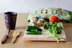 Fresh vegetables on wood table. Photograph of some fresh vegetables on a wood table with a Mexican hand crafted blouse royalty free stock image