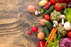 Fresh vegetables on wooden background. Collection of mixed organic vegetables and herbs on old wooden background Royalty Free Stock Image