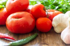 Fresh vegetables on a wooden background. Healthy eating. Food tomato green red pepper broccoli colorful freshness onion parsley radish raw diet eggplant garlic stock photography