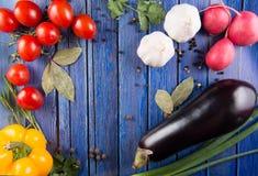 Fresh vegetables on wooden background. Fresh vegetables and spices on a blue wooden background Stock Image