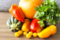 Fresh vegetables on a wooden board. Pumpkin, zucchini, pepper and parsley on a wooden background Stock Images