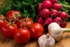 Fresh vegetables on a wooden board. Fresh vegetables on wooden board tomatoes, radishes and garlic, greens Royalty Free Stock Photography