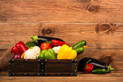 Fresh vegetables in the wooden box on the rustic background. Fresh vegetables in the box on the rustic background Royalty Free Stock Photo