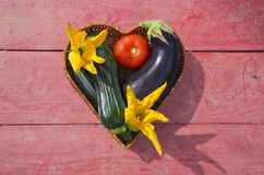 Fresh vegetables in wooden heart form basket on table Stock Photography