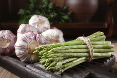 Fresh vegetables on a wooden oak board in a rustic interior. Fresh asparagus and garlic on a wooden oak board in a rustic interior. A shelf with a clay pot and stock image