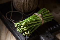 Fresh vegetables on a wooden oak board in a rustic interior. Fresh asparagus and garlic on a wooden oak board in a rustic interior. A shelf with a clay pot and stock photo