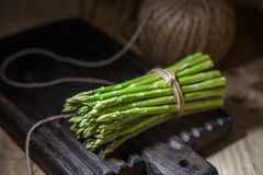 Fresh vegetables on a wooden oak board in a rustic interior. Fresh asparagus and garlic on a wooden oak board in a rustic interior. A shelf with a clay pot and royalty free stock photography