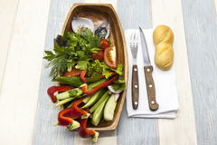 Fresh vegetables on a wooden plate with fork and knife. Red pepper, tomato, cucumber, radish, parsley, dill healthy diet. Fresh vegetables on a wooden plate Stock Images