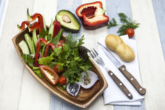 Fresh vegetables on a wooden plate with fork and knife. Red pepper, tomato, cucumber, radish, parsley, dill healthy diet. Fresh vegetables on a wooden plate Royalty Free Stock Image