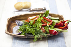 Fresh vegetables on a wooden plate with fork and knife. Red pepper, tomato, cucumber, radish, parsley, dill healthy diet. Fresh vegetables on a wooden plate Stock Photo