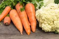 Fresh vegetables on wooden table. Harvesting background. Carrots and cauliflower Royalty Free Stock Images