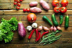 Fresh vegetables on a wooden table. Fresh vegetables lying on an old rustic wooden table with one source of light from the top. View from above Royalty Free Stock Photography