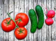 Fresh vegetables on wooden table. Fresh tomatoes cucumbers and radish seved on wooden table Stock Photos