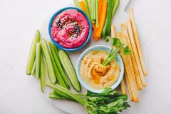 Fresh vegetarian dips in small bowls on table. Appetizing vegetarian healthy dips sauces in small bowls with cut vegetables on cutting board. View from above stock images