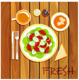 Fresh vegetarian dishes on wooden table. Healthy vegetarian lunch served on wooden table with fresh vegetable salad with tomatoes, cucumbers and onion, grated Royalty Free Stock Photography