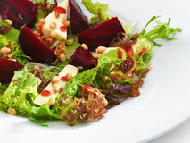 Fresh vegetarian gourmet salad with baked beetroot and cheese. Served on a white round plate Royalty Free Stock Photo