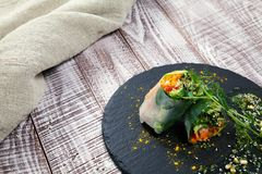 Fresh vegetarian roll with vegetables herbs and spices on a black board and wooden background. royalty free stock photography