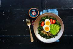 Quinoa, kale and egg bowl. Fresh vegetarian salad bowl of quinoa, kale, tomatoes, avocado and egg over black wooden background, top view, copy space. Flat lay Stock Image