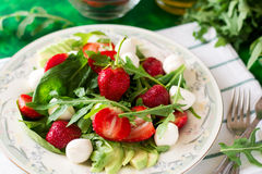 Fresh vegetarian salad with spinach, arugula, avocado slices, strawberries and mini mozzarella. On green wooden table. Selective focus stock photography