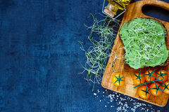 Fresh vegetarian sandwich. Delicious vegetarian sandwich with whole grain bread, alfalfa and guacamole on rustic wooden cutting board over dark vintage table Stock Photos