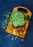 Fresh vegetarian sandwich. Top view of fresh vegetarian sandwich with whole grain bread, alfalfa and guacamole on rustic wooden cutting board over dark vintage Stock Images