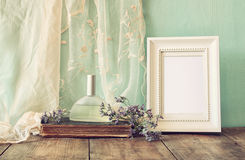 Fresh vintage perfume bottle next to aromatic flowers and antique blank frame on wooden table. retro filtered image Stock Images