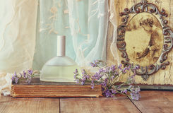 Fresh vintage perfume bottle next to aromatic flowers and antique frame with old photography on wooden table. retro filtered image Royalty Free Stock Photos