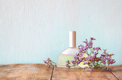 Fresh vintage perfume bottle next to aromatic flowers on wooden table. retro filtered image Stock Images